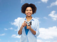 happy african american woman with film camera