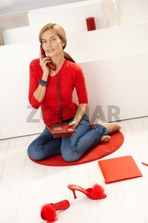 Young female talking on phone in red pullover