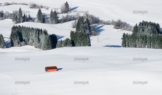 Orange barn building in white snow landscape. Aerial view of rural countryside on snowy winter day. Weitnau, Allgau, Bavaria, Germany.
