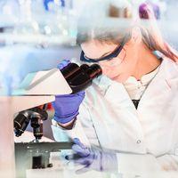 Life science researcher microscoping in genetic scientific laboratory.