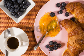 Closeup of croissant, blueberries, coffee and jam over a tablecloth