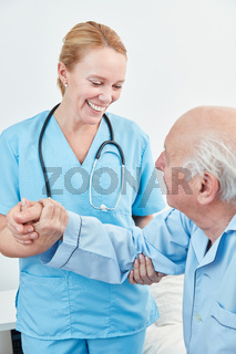 Pflegekraft hilft altem Mann beim Aufstehen