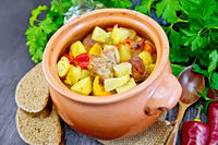 Roast meat and vegetables in clay pot on board