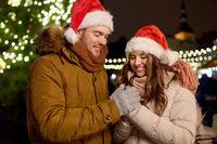 happy couple in santa hats at christmas tree