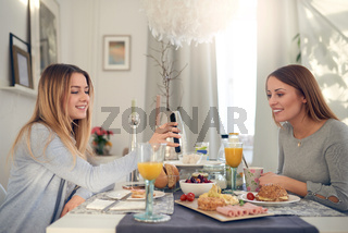 Teenager showing her mother her mobile phone