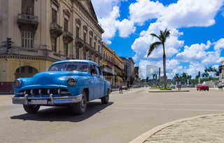 Blauer amerikanischer Oldtimer fährt auf der Hauptstraße an der historischen Häuserfront vorbei - Se