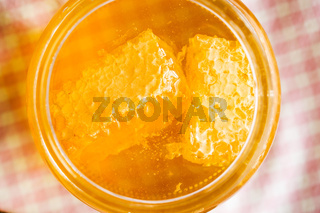 Honeycomb in jar with honey.