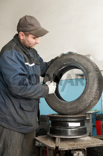 repairman lubricating car tyre