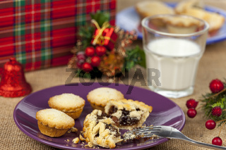 Broken mince pie and milk on a christmas table