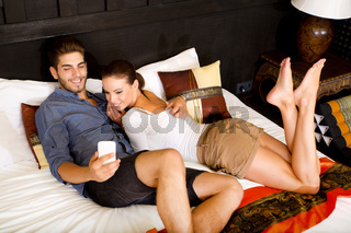Young couple using phone in a asian hotel room