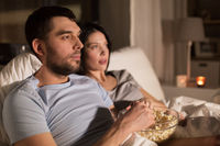 couple with popcorn watching tv at night at home
