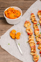 Skewers of grilled chicken satay with red peppers and onions