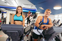 Young couple running on bikes in fitness gym