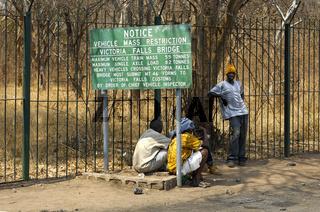 Einheimische an einem Informationsschild mit Angaben zur Gewichtsbeschränkung für den Schwerverkehr bei der überquerung der Victoria Falls Brücke zwischen Simbabwe udn Sambia