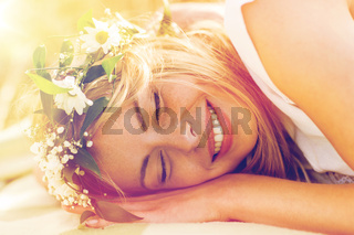 happy woman in wreath of flowers lying
