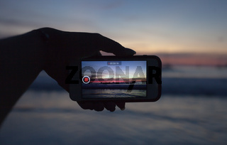 Hands holding mobile smart phone and take a video of the sunset in summer time