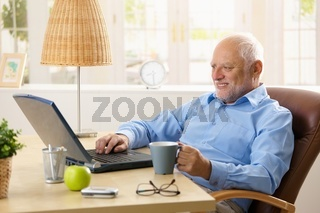 Smiling senior man using laptop