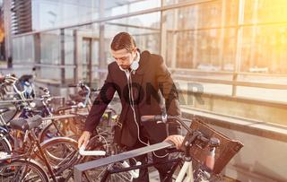 Business Mann stellt Fahrrad an Fahrradständer
