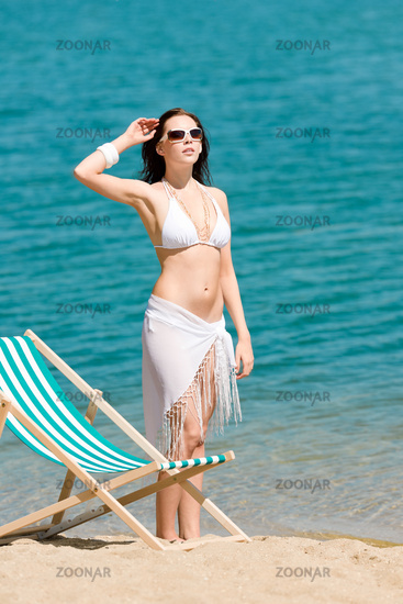 Summer toned woman sunbathing on beach in bikini