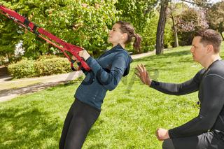 Frau mit Personal Trainer macht Schlingentraining