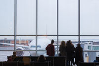 People waiting for airplane departure on a rainy day.