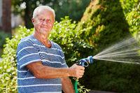 Senior im Garten beim gießen