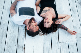 man and woman lie on the wooden floor