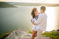 Couple wearing on dress with a pattern at beautiful landscape, on cliff with sunset in love.