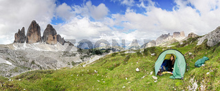 Woman sitting in tent smiling happy. Great mountains. Tre Cime.