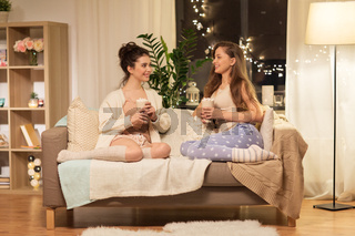 happy female friends drinking cacao at home