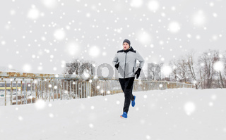 man running along snow covered winter bridge road