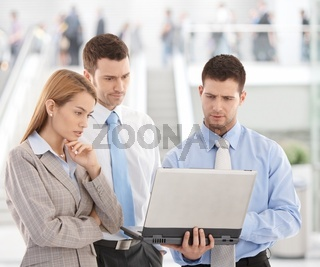 Young businesspeople looking at laptop screen