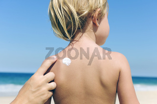Sommerferien: Mutter cremt Kind mit Sonnencreme am Strand ein