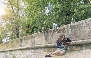Young woman reading a book on a wall