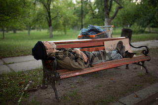 View of old man lying on bench in city park.