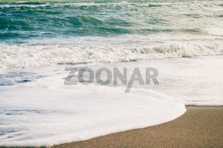 Sea waves and sand on the beach in retro colors