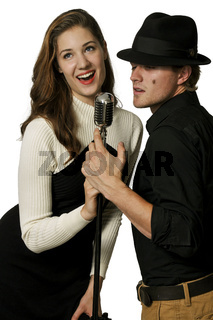 Man and woman singing into microphone