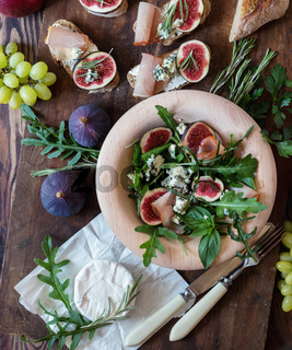 Easy diet salad with arugula, figs and blue cheese on a brown wooden surface. Sandwiches with ricotta, fresh figs, prosciutto, rosemary and blue cheese. Delicious fruity breakfast, top view