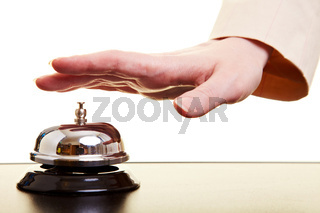 Hand drückt auf Hotelglocke