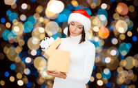 displeased woman in santa hat with christmas gift