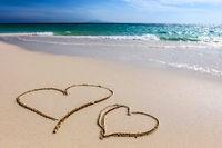 Hearts drawn sandy beach