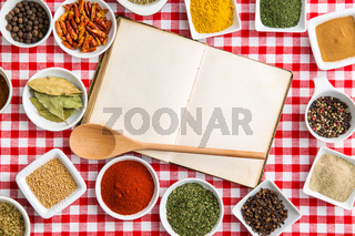 Blank cookbook and various spices.