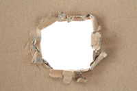 Ripped hole in brown cardboard