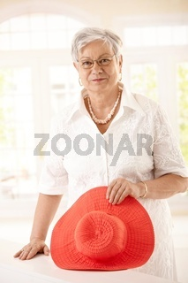 Portrait of senior woman holding hat