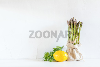 Bunches of fresh asparagus in a little sack, lemon and fresh parsley on the white cracked wall background. Copy space