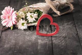 Flowers wrapped in newspaper and a heart