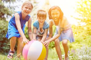 Drei Mädchen rollen Ball im Sommer