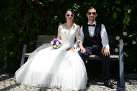just married young couple sitting on a bench