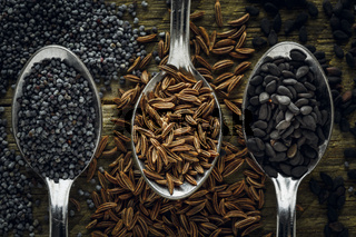 Poppy, cumin and black sesame seeds in a spoons