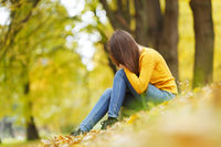 Woman sitting on autumn leaves